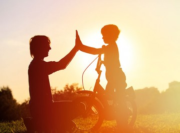 boy-on-bike-man-high-five-orange-silouhette_773x532
